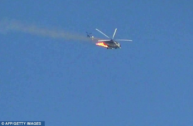 The Syrian army helicopter goes into a tailspin after being hit by a rebel rocket over Damascus. It leaves a trail of smoke through the sky with fire ripping through its body