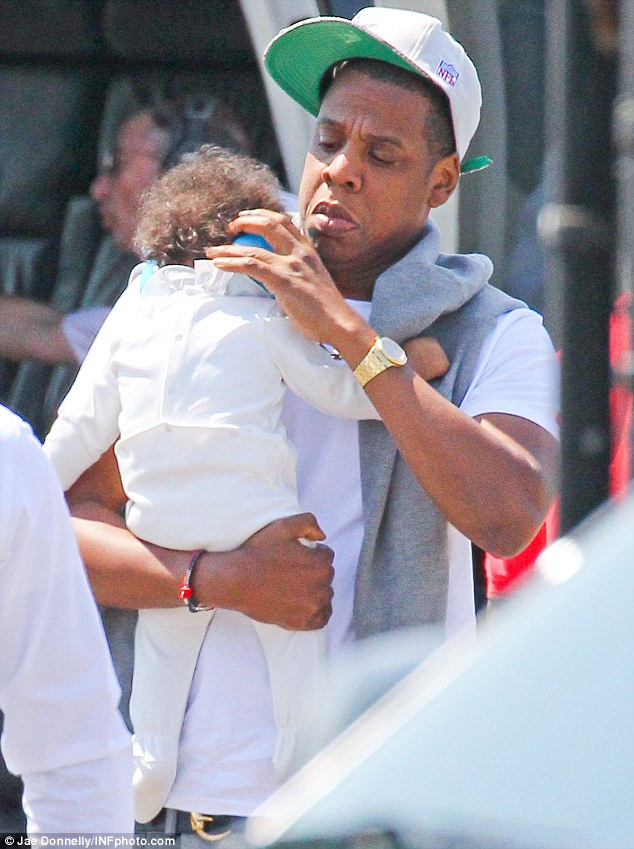 Attentative: Jay Z checks on his daughter, Blue Ivy Carter, after they arrive in New York by helicopter, she's wearing earphones to protect her delicate shell-likes from the noise
