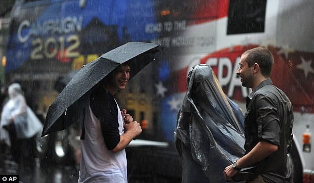 A man uses a plastic trash bag for rain protection at the Carolina Fest street fair, on the eve of the Democratic National Convention (DNC) on September 3, 2012 in Charlotte, North Carolina