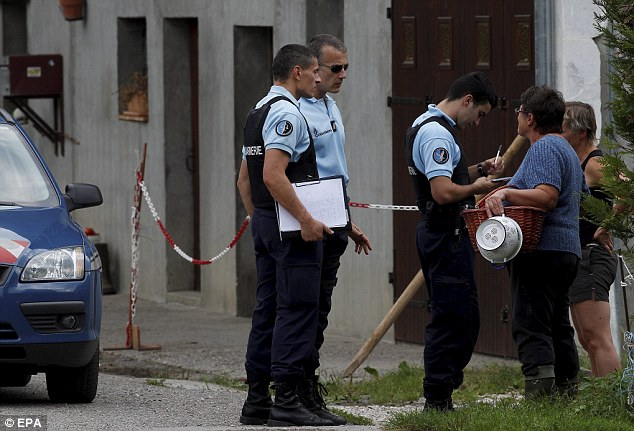 French Police officers talk to locals close to the spot where the massacre happened. A French source said the four-year-old was found hiding underneath her mother's legs. The two other bodies were believed to be those of her father and grandmother