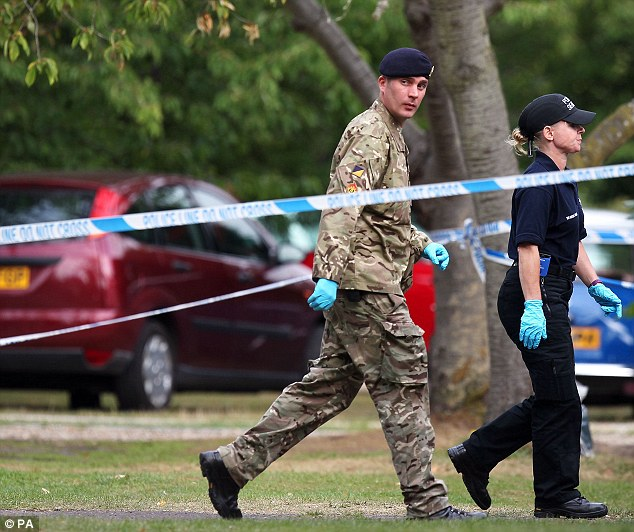 A member of the Royal Logistic Corps bomb disposal team walks with a police officer close to the home of Saad al-Hilli in Claygate, Surrey as the investigation deepens