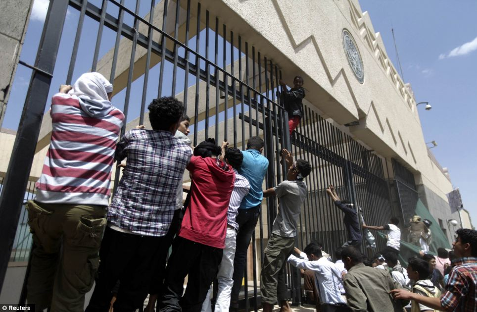 Fervent belief: Protesters climb a fence surrounding the U.S. embassy in Sana'a as they fight to discredit the 'blasphemous' film