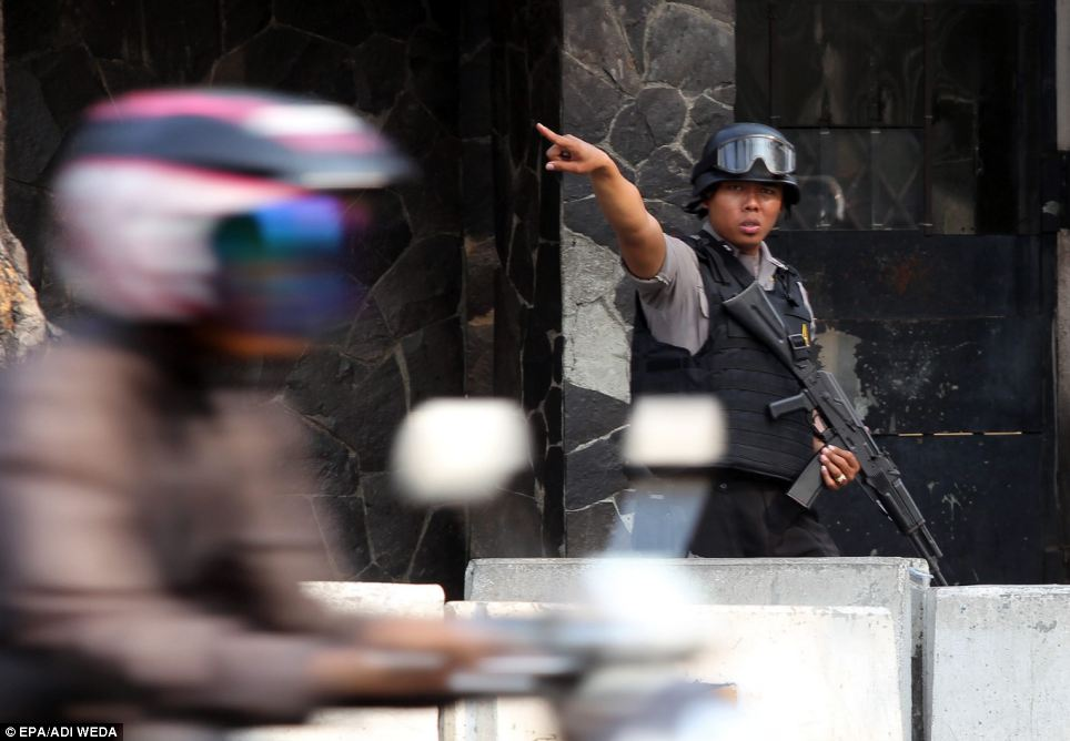 Prepared: An armed guard stands outside the U.S. ambassador's residence in Jakarta as security was stepped up outside the building in response to Muslim protests in other countries