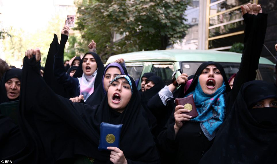 Aggression: The women shout anti-US slogans while holding copies of the holy book at the Swiss embassy