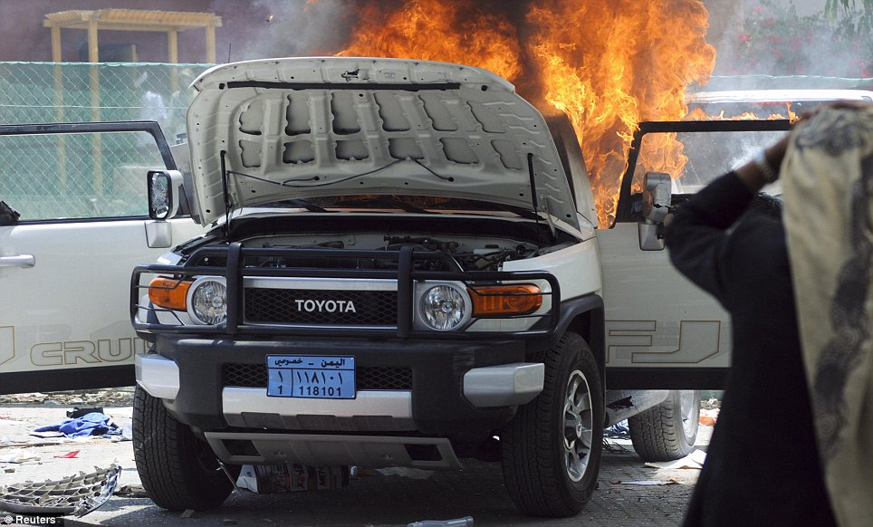 City in flames: A man stands in front of a vehicle burning at the U.S. embassy in Sana'a after demonstrators attacked the U.S. Embassies in Yemen on Thursday in protest at a film they consider blasphemous to Islam