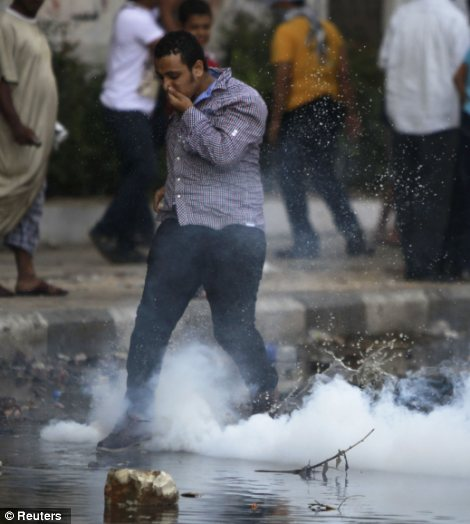 A muslim thug reacts from a tear gas canister thrown by riot police