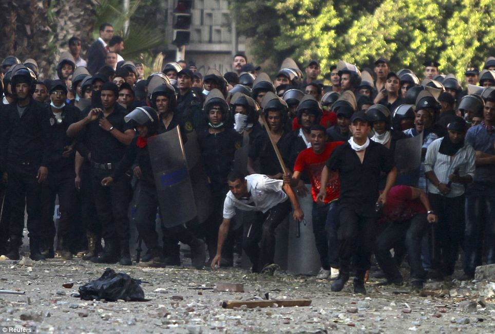 You shall not pass: Riot policemen throw stones during clashes with protesters along a road leading to the U.S. embassy