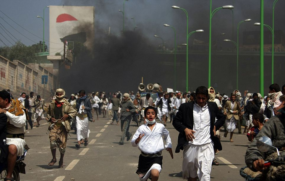 Yemeni protesters run for cover from tear gas fired by riot police during a demonstration against a film mocking Islam at a crossroad leading to the US embassy