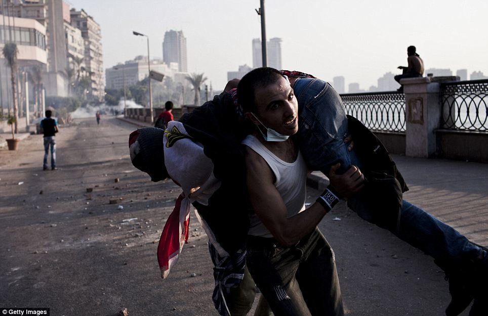 Cairo: An Egyptian protester carries away another demonstrator overcome by exposure to tear gas during clashes near the United States Embassy
