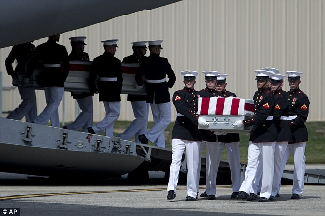 Carry teams move metal coffins holding the remains of the four Americans killed this week in Benghazi, Libya, from a transport plane on Friday