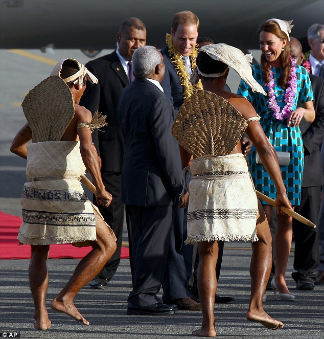 In good spirits: The royal couple laugh as warriors perform a traditional dance at Honiara International Airport as they vowed to prosecute those responsible for taking and printing the naked pictures