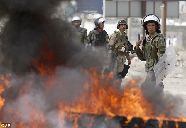 Up against it: Afghan riot police stand by burning tyres as they battle to fend off the protesters