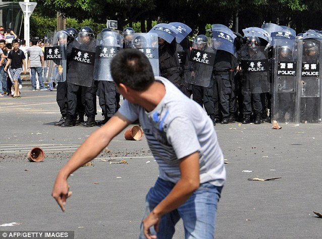 A demonstrator throwing flowerpots towards the police as thousands of protesters took to the streets on Saturday