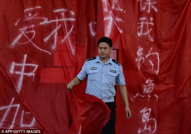 A Chinese policeman emerges from a closed Japanese restaurant covered with Chinese national flags and banners saying 'it is Chinese-owned'