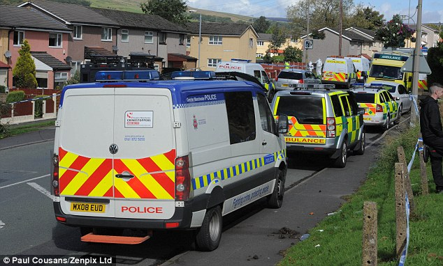 Convoy: Police vehicles and ambulances line the street close to where two unarmed officers were shot dead