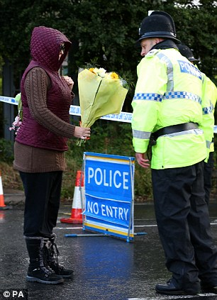 A police officer is given flowers, by a member of the public
