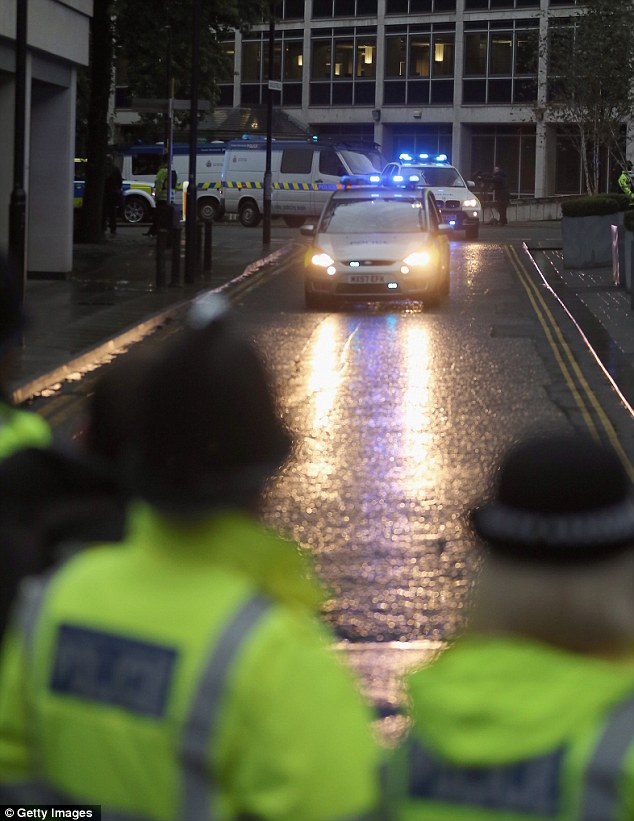 Case: The convoy sped in at around 8am, where its lights cut through the gloom as police officers watched on