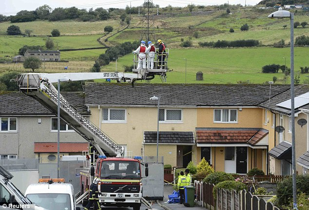 Probe: A fire engine lifts forensic offices above the house where two female police officers were shot, in Hattersley near Manchester