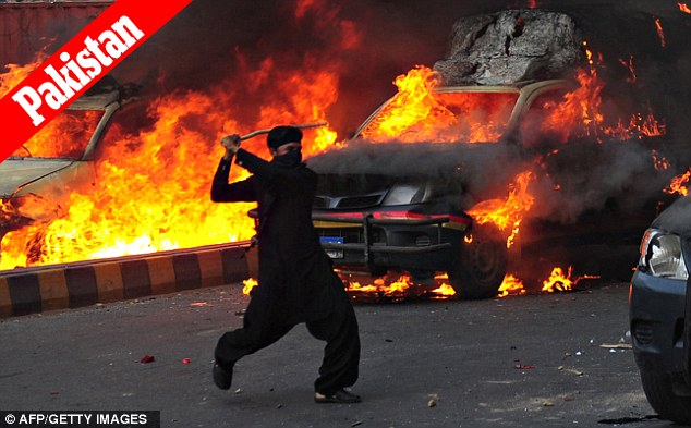 Flames of fury: A Muslim demonstrator brandishes a stick near burning police vehicles during the protest against an anti-Islam film in Karachi