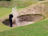 A golfer plays out of a bunker