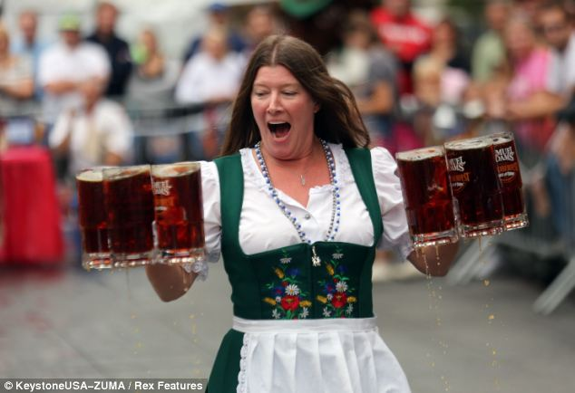 Traditional games: Hanna Marie Harten takes part in a beer stein race as part of the festivities at Oktoberfest¿Zinzinnati