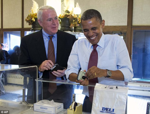Flush with cash: Barack Obama, pictured with Milwaukee mayor Tom Barrett, pulls out a wad of bills to pay for a purchase of sausages at a Wisconsin deli