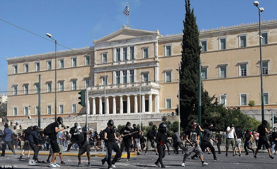 The Greek Parliament building provides the backdrop as demonstrators clash with police following a union-organised rally opposing new austerity measures