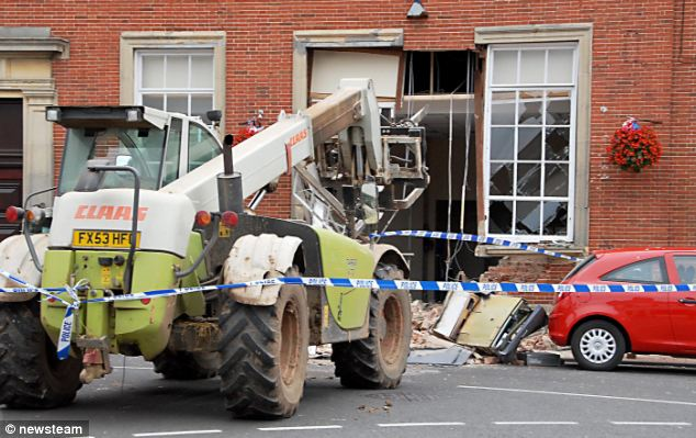 Thieves used this stolen four-tonne digger to rip out a Barclays cash machine, leaving a gaping 12ft hole in the bank's wall
