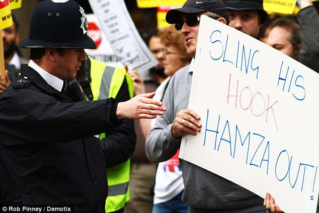 Protest: A man in favour of the extradition of Abu Hamza stands among protesters with the sign 'Sling His Hook, Hamza Out!' outside the Royal Courts of Justice