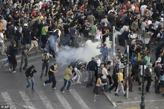 Flee: Protesters, some wearing masks, are forced back by riot police's tear gas