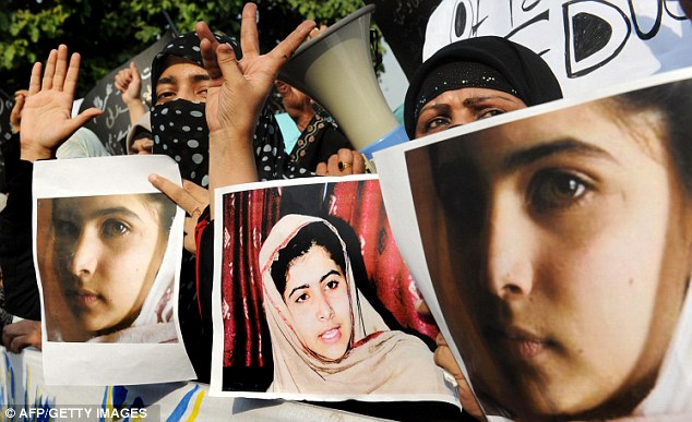 Outrage: Activists carry photographs of Malala Yousafzai during a protest rally against her assassination attempt in Lahore today