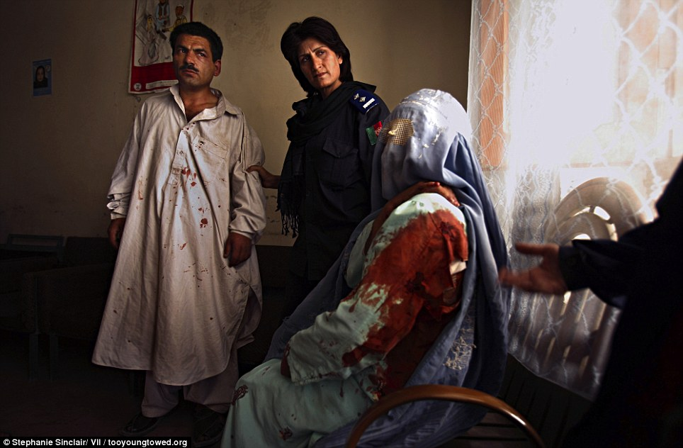 Gruesome: Police woman Malalai Kakar (back right) arrests Janan, 35, after he tried to kill his 15-year-old wife Jamila for angering him by fleeing her home to stay with her mother following years of abuse