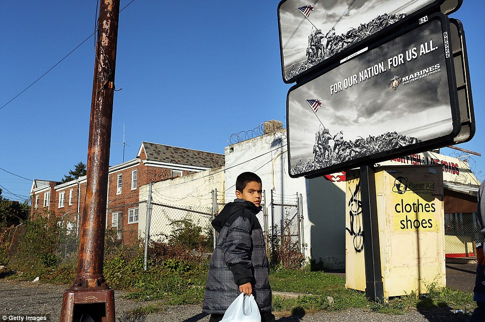 A child walks down a street in impoverished Camden, which sits just over the bridge from more affluent Philadelphia