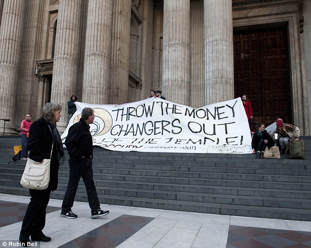 Demands: Outside, other Occupy members held up a banner on the cathedral's steps
