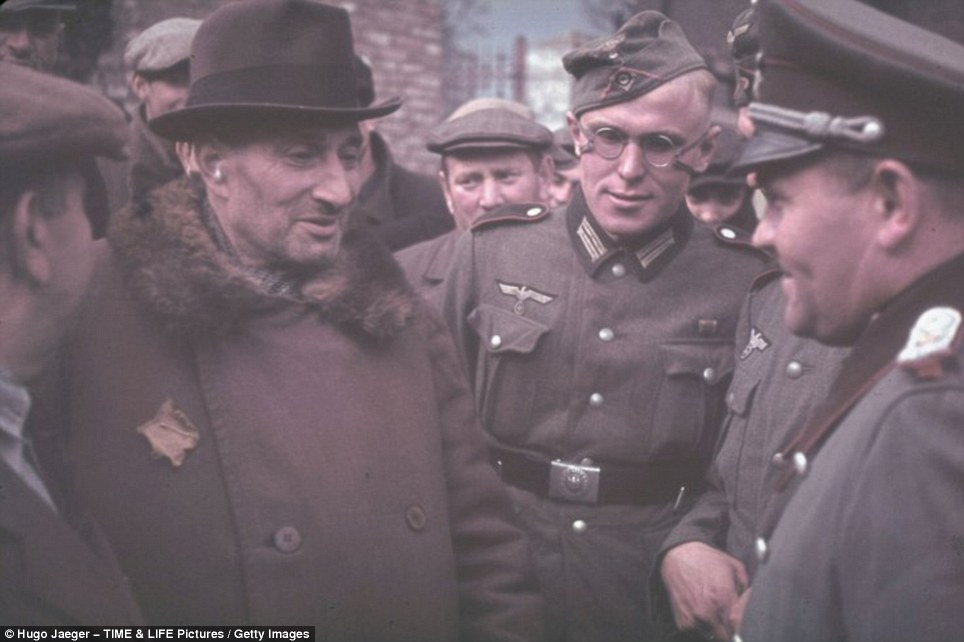 An elderly man with a yellow Star of David fixed to his chest, speaks with German officers as he and other Jews are rounded up in Kunto, German-occupied Poland in 1939
