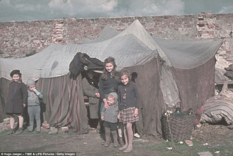 Innocent victims: These young Jewish girls couldn't possibly have imagined horrors lay ahead as pose outside their tent in another haunting photograph taken by the ardent Nazi Hugo Jaeger
