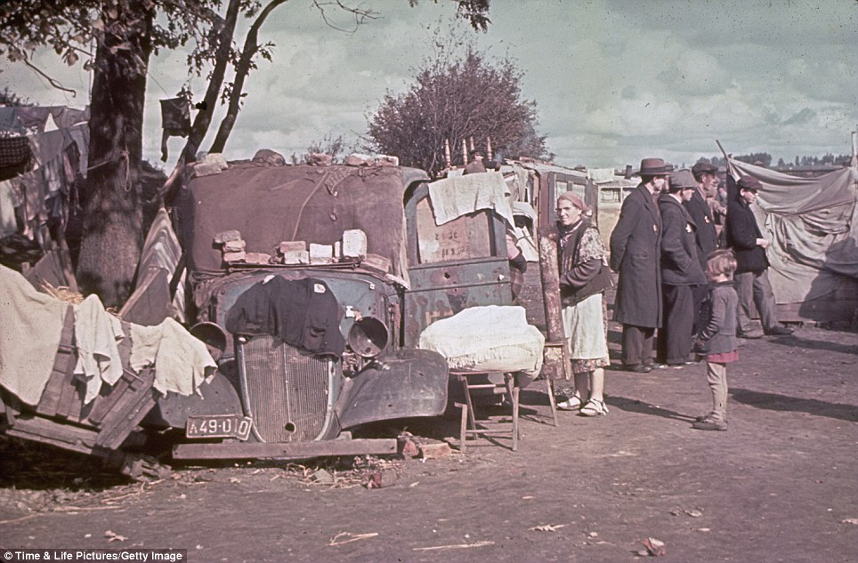 Makeshift dwelling: Jewish inhabitants of the Kutno Ghetto stand near a car which has been converted into a makeshift house in early 1940