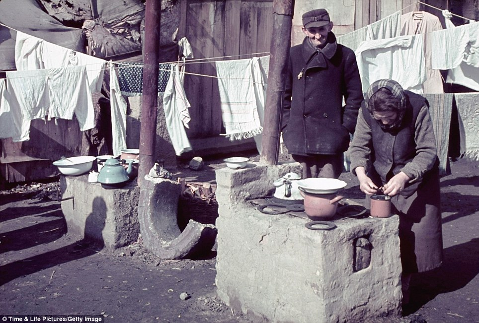 An elderly Jewish woman bends over outdoor rubble that serves as a kitchen while a man, his Star of David badge clealry visible, watches over her in the Kutno Ghetto