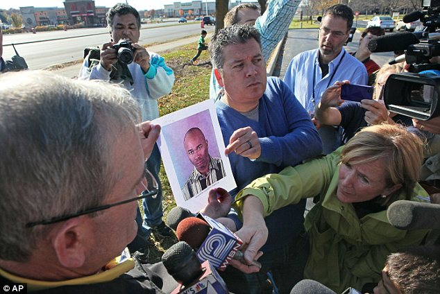 First picture: Reporters surround Brookfield police Lt Mark Millard, pictured left holding a photo of shooting suspect Radcliffe Haughton, as he answers questions at a news conference