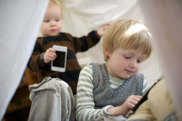 A brother, aged 4, and sister, aged 1, play with an iPad and iPhone. Researchers today said that giving children access to electronics at night is disrupting their sleep patterns.