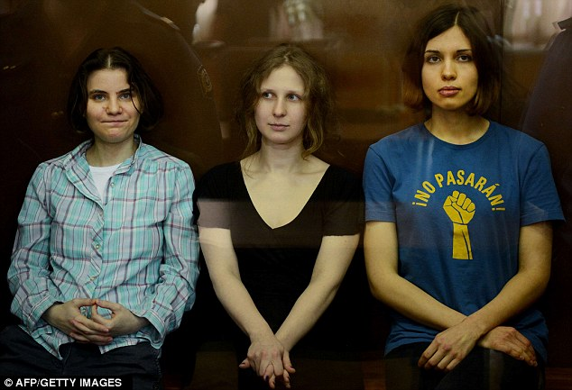 Jailed: Members of Pussy Riot sit in a glass-walled cage during a court hearing in Moscow earlier this year. Nadezhda Tolokonnikova, right, Maria Alyokhina, centre, and Yekaterina Samutsevich left, are pictured