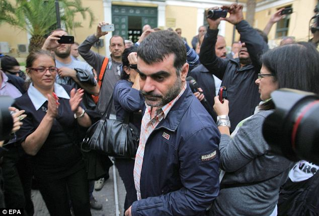 Show of support: Supporters applaud Mr Vaxevanis who likened his arresting officers to Nazi stormtroopers
