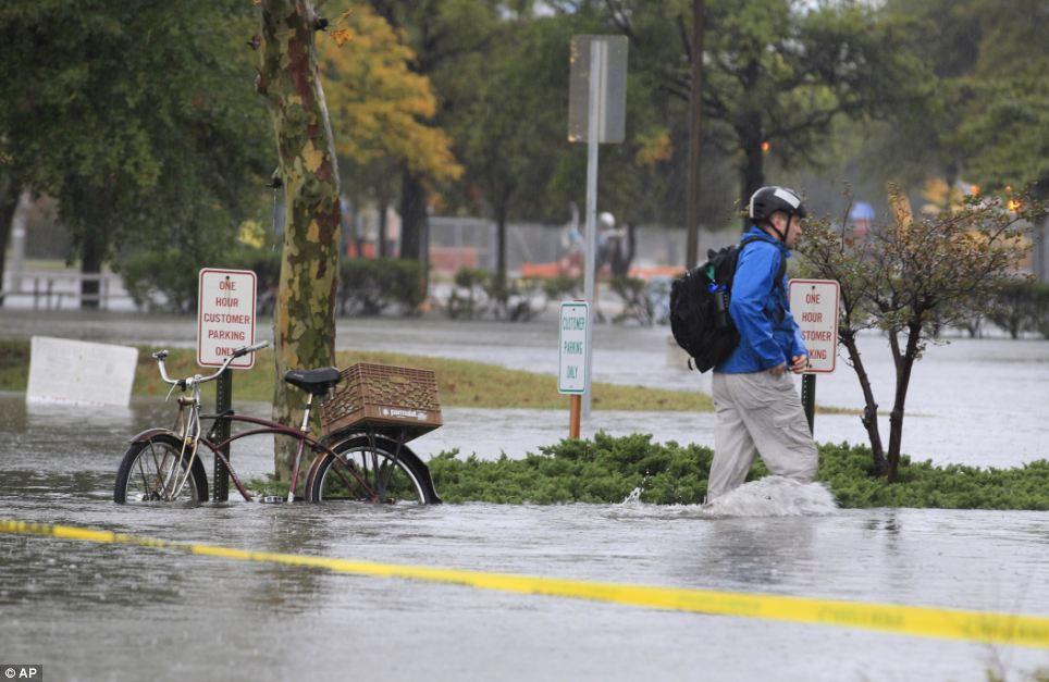 Sumergido: A las cadenas de residentes en Norfolk en su bicicleta y se dirige a trabajar cerca del centro de Virginia después de la lluvia de arena y aguas de la inundación afectó a la zona