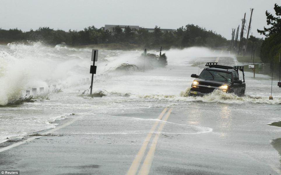 Inundaciones: A través de las unidades de camiones de agua empujado por un camino de arena por el huracán en Southampton, Nueva York, el lunes, mientras la tormenta se acelera