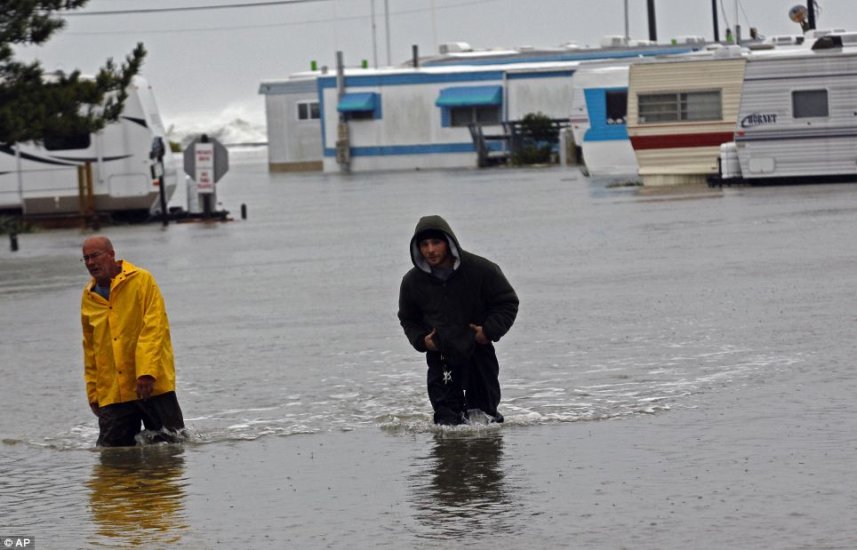 El aumento de las aguas: Terry Robinson, a la izquierda, y Bobby Carnutte vadear a través de agua de la inundación en RV Park en Kitty Hawk, Carolina del Norte, donde las carreteras son intransitables