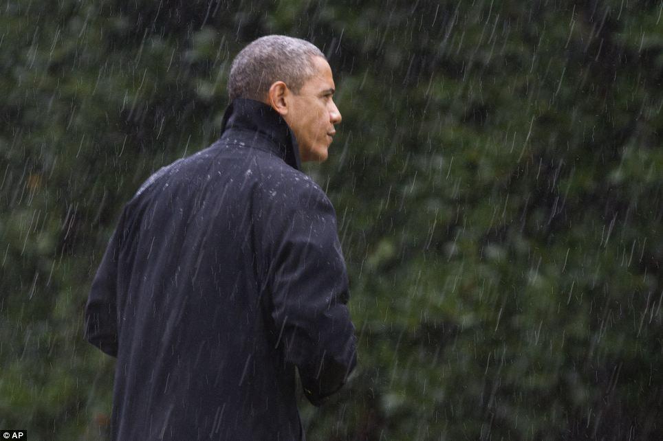 Bajo una nube: Después de cancelar su aparición en un acto de campaña mañana en Orlando, Florida, el presidente Obama se acerca a la Casa Blanca bajo la lluvia