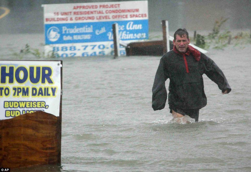 Treacherous: Después de comprobar para asegurarse de que su línea de barco es seguro, Bob Casseday cruza la calle inundada justo sobre el puente a lo largo de Savannah Road en Lewes, Delaware