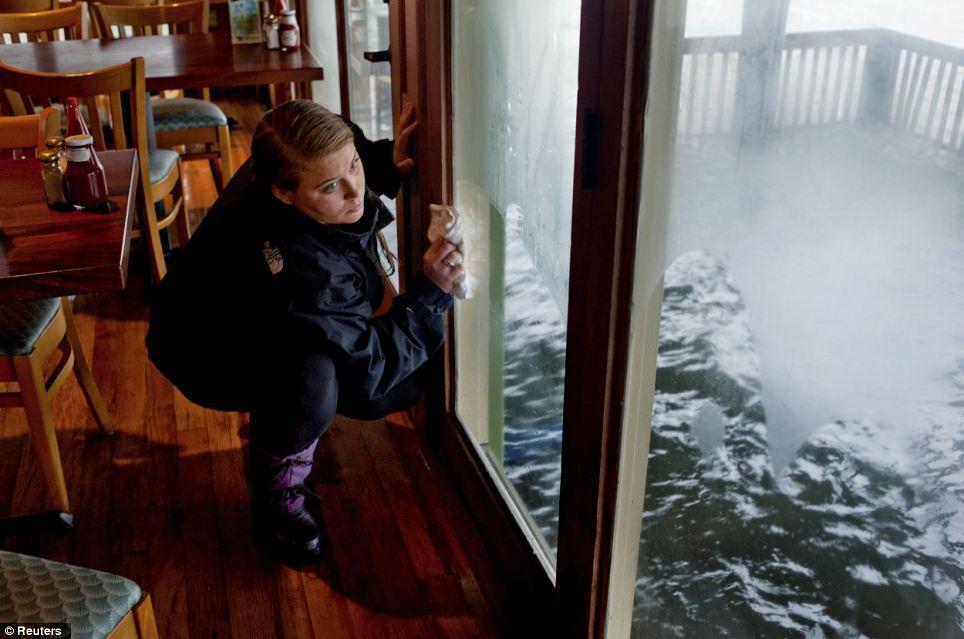 El aumento de las aguas: Angelique Hionis limpieza después de las inundaciones ocurrieron en el restaurante de mariscos de Bubba y Crabhouse del huracán de arena en Virginia Beach, Virginia