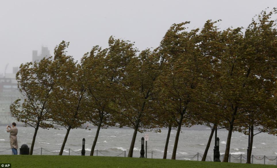 Potente: Una mujer toma una fotografía del río Hudson como ráfagas de viento dobla los árboles en Hoboken, Nueva Jersey
