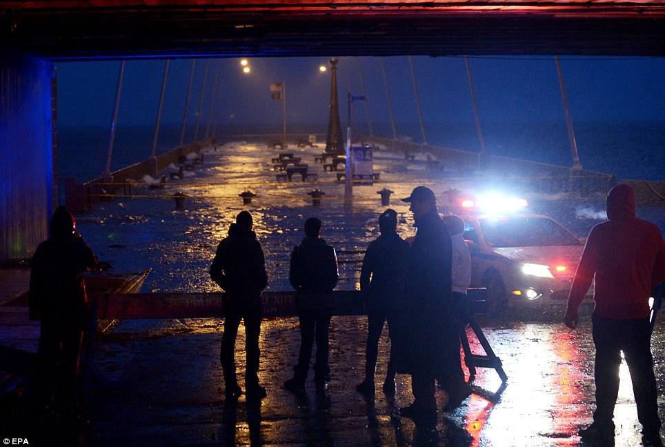 Cerró de golpe: las personas se refugian en el muelle inundado como los efectos del huracán de arena se hacen sentir en Rockaway Beach, New York
